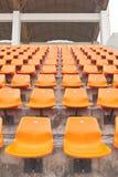 Columns of orange plastic stadium seats Royalty Free Stock Photo