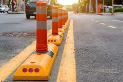 Columns with a reflective layer and yellow road marking separates the cycle path from the automobile part of the road. Safety of stock photography