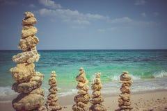 Columns from sea stones on the beach Stock Photo
