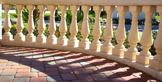 Columns in Sunshine & Shadows. Decorative banister in model home along brick driveway royalty free stock photo