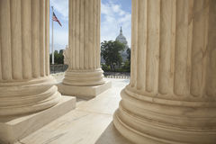 Columns of the Supreme Court with an American flag and the US Ca. Close up of the columns  of the Supreme Court building with an American flag and the US Capitol Stock Photography
