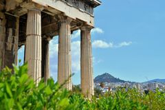 Columns of the Temple of Hephaestus with view of Athens in the background. Columns of the Temple of Hephaestus with vegetation. Shot on a sunny day, the sky is stock images