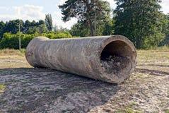 A coluna cinzenta concreta encontra-se na terra na grama Imagens de Stock