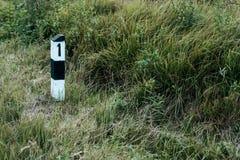 Coluna concreta com número um, gramado verde na borda da estrada, conceito do fundo do começo do trajeto A ideia de fotografia de stock royalty free