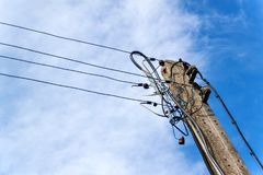Coluna concreta da linha elétrica Conexão elétrica caótica Emaranhado dos fios fotos de stock