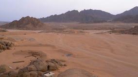 A coluna de uma bicicleta do quadril?tero monta atrav?s do deserto em Egito no contexto das montanhas Conduzindo ATVs filme