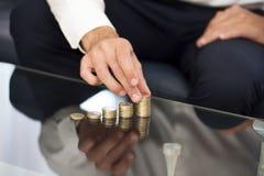 Coluna do dinheiro da construção da mão do homem de negócios Foto de Stock