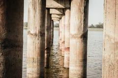 Colunas da arquitetura urbana da ponte, feitas do concreto de grande resistência em um rio tomado de um canteiro de obras O concr fotografia de stock