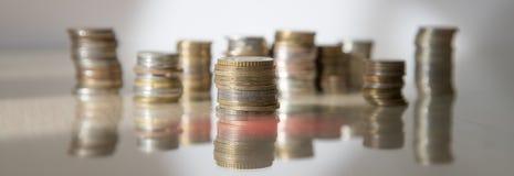 Colunas das moedas de ouro, pilhas das moedas na tabela de funcionamento fotografia de stock