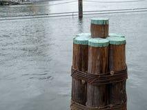 Colunas de madeira da doca que sentam-se perto de um cais na doca local imagem de stock