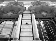 Colunas de pedra com indicadores que refletem a cidade Imagem de Stock Royalty Free