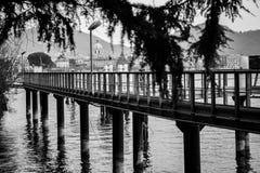 Colunas do cais na frente da paisagem de Como Fotografia de Stock Royalty Free