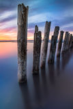 Colunas incomuns na água no fundo do céu colorido foto de stock royalty free