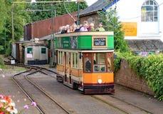 COLYTON, DEVON, ENGELAND - AUGUSTUS ZESDE 2012: Een oranje en groene tram trekt in Colyford-post op het Seaton-tramspoor passagie stock foto's