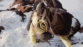 Com a ajuda das cordas esticadas para cima, um montanhista experiente ascensão uma inclinação da neve e umas rochas de projeção n filme