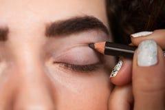 Com a ajuda de um lápis cosmético, pinte uma linha grossa em seu vinco cortado imagem de stock royalty free