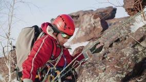 Com a ajuda de uma corda forte, um montanhista novo desce abaixo de uma inclinação de pedra íngreme vídeos de arquivo