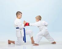 Com as folhas de prova no karateka das mãos no karategi bate o perfurador em simuladores Imagens de Stock