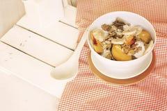 Com a bacia de cereal e de fruto na toalha de mesa alaranjada Fotografia de Stock