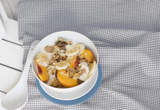 Com a bacia de cereal e de fruto na toalha de mesa alaranjada Foto de Stock