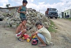Com brinquedo transporta o jogo de meninos do latino e do caminhão real Imagem de Stock