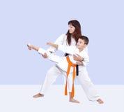 Com cinturão negro o instrutor ensina o atleta bater um pontapé Imagens de Stock Royalty Free