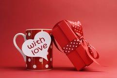 Com mensagem do amor na caneca vermelha e no vermelho do às bolinhas Imagens de Stock