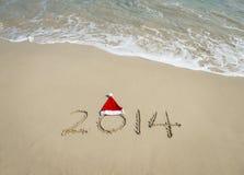 2014 com o chapéu de Santa na areia da praia do mar Imagens de Stock