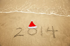 2014 com o chapéu de Santa na areia da praia do mar Fotografia de Stock Royalty Free