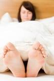 Com os pés descalços na cama Imagem de Stock Royalty Free