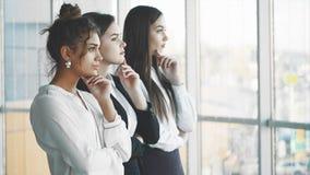 Com prazer, três mulheres de negócio cruzam seus braços, olhando a câmera