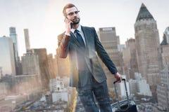 Com pressa Retrato do homem de negócios seguro novo no terno que puxa a bagagem e que fala pelo telefone ao andar fora fotografia de stock