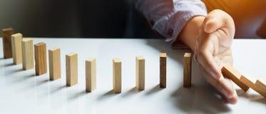 COM ruída dos dominós da parada da mão do homem de negócios, panorâmico contínua Foto de Stock Royalty Free