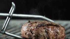 Com tenazes de brasa do ferro eu viro um rissol suculento grande da carne na grade video estoque