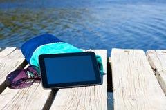 Com um PC da tabuleta no lago fotografia de stock royalty free