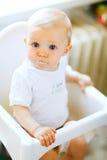 Coma al bebé manchado en la silla que mira impresionante foto de archivo libre de regalías
