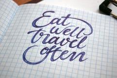 Coma bem e viaje fundo frequentemente caligráfico Fotos de Stock Royalty Free