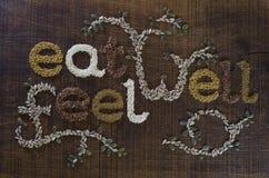 Coma bem, seja bem escrito e decorado nas sementes Imagem de Stock