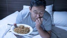 Coma a la medianoche, el mún hábito alimentario, cena de última hora en cama foto de archivo