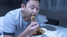 Coma a la medianoche, el mún hábito alimentario, cena de última hora en cama imagen de archivo