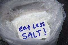 Coma menos sal para el montón del concepto de la salud de la sal en fondo de la bolsa de plástico foto de archivo libre de regalías