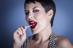 Coma, mujer joven feliz con el lollypop en su boca en backg azul Imagen de archivo