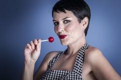 Coma, mujer joven feliz con el lollypop en su boca en backg azul Fotos de archivo libres de regalías