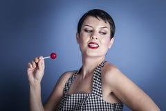 Coma, mujer joven feliz con la piruleta en su boca en backg azul Fotografía de archivo libre de regalías