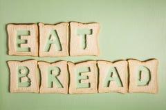 Coma o texto do pão cinzelado fora das fatias do pão branco Imagem de Stock Royalty Free