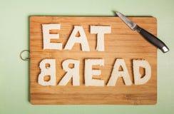 Coma o texto do pão cinzelado fora das fatias do pão branco Imagem de Stock