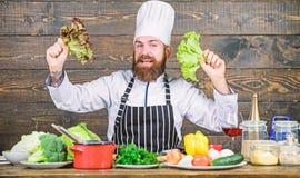 Coma sano Concepto de dieta Lechuga del sombrero del desgaste de hombre y del control del delantal Nutrici?n sana Cocinero profes fotos de archivo