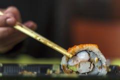 Coma uma parte de sushi com hashis imagem de stock royalty free