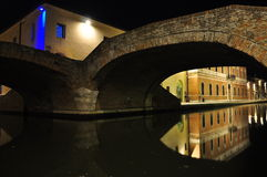 Comacchio, canal bridge by night. Ferrara, Italy. A bridge over a canal in Comacchio. Colourful houses by night Stock Photos