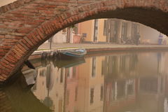 Comacchio, canal bridge in winter. Ferrara, Emilia Romagna, Italy. A bridge over a canal in the colorful Italian village of Comacchio. Old brick bridge across Royalty Free Stock Photo